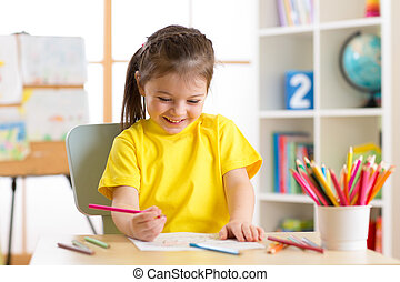 Cute little preschooler child girl drawing color pencils at...