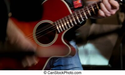 Musician at rock concert - guitarists plays red acoustic guitar in night club, close up