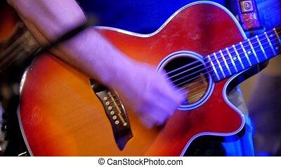 Musician at rock concert - guitarists plays acoustic guitar...
