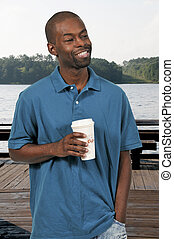 Black Man Drinking Coffee - Young handsome African American...