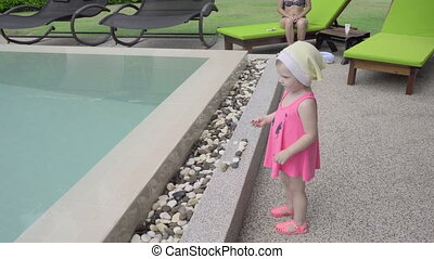 Two-year-old girl near hotel pool - Two-year-old girl with...