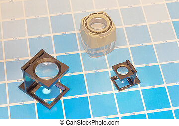 Three magnifier or printer's loupe sits on a cyan test sheet...