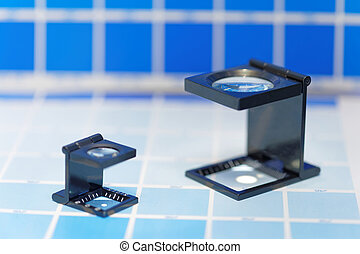Two magnifier or printer's loupe sits on a cyan test sheet...