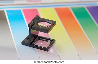 Magnifier or printer's loupe sits on a colorful CMYC test...