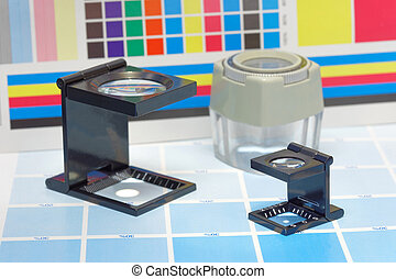 Three magnifier or printer's loupe sits on a test sheet -...