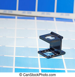 Magnifier or printer's loupe sits on a cyan test sheet
