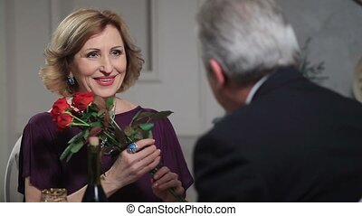 Smiling senior woman receiving flowers from man - Cheerful...