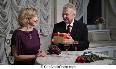 Handsome senior man giving present to his wife