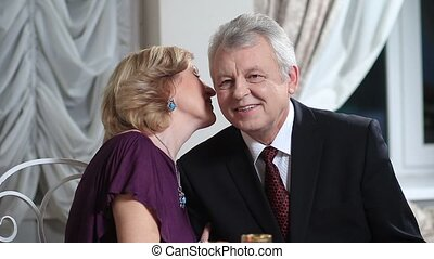 Smiling elderly woman whispering to husband - Happy...