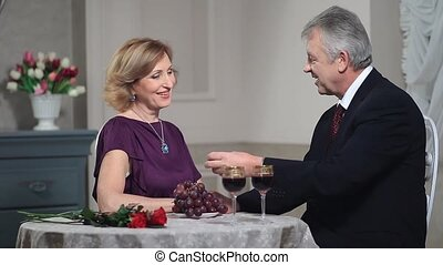 Mature woman feeding man with grapes at restaurant