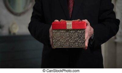 Senior person holding a gift pack - Middle section of...
