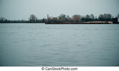 Time lapse of long cargo barge moving on Dnieper river in...