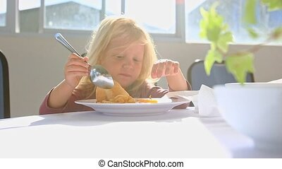 Little Blond Girl Eats Chicken with Large Spoon at Table