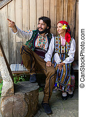 Bulgarian costumes - Young happy couple sitting in...
