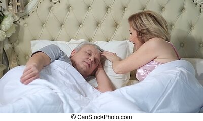 Wife waking up her husband in the morning - Beautiful senior...