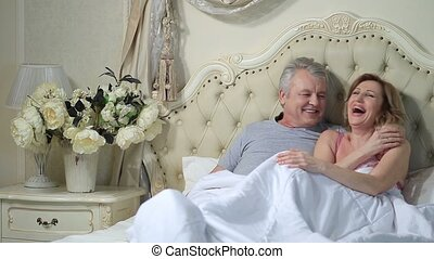 Excited senior couple laughing together in bed - Cheerful...