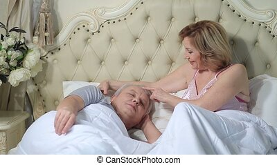 Woman gently waking up man in the morning - Happy senior...