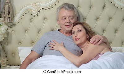 Couple lounging in bed after awaking cuddling - Cheerful...