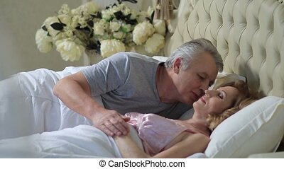 Senior man waking up his wife with kiss