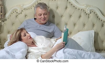 Senior couple reading a book in bed - Relaxed elderly woman...