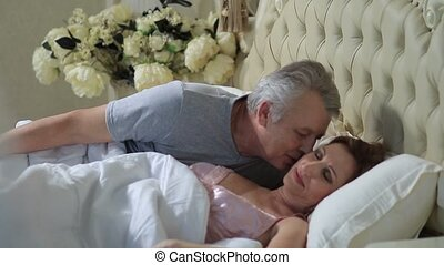 Mature loving couple lounging in bed after awaking -...