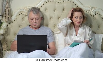 Senior couple relaxing in bed with laptop and book - Smiling...