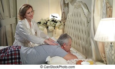 Mature woman giving massage to senior man in bed -...