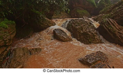 Cascade of Stormy Mountain Brown Water River among Stones -...