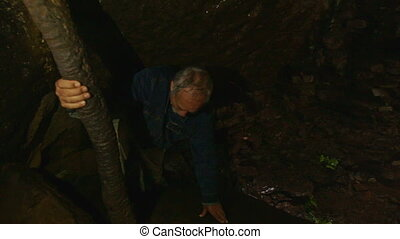 Closeup Old Man Holds Trunk Tries to Get out Dark Cave -...