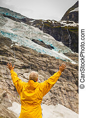 Tourist admiring Boyabreen Glacier in Norway - Adventure...