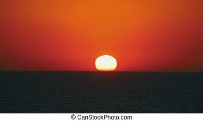 Sunset over the Sea - Sunset orange sun over the surface of...
