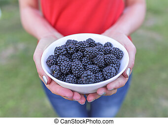 Girl holding a bowl of blackberries. - A girl holding a bowl...