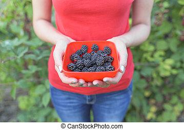 Girl holding a bowl of blackberries.
