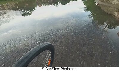 Biker on bicycle riding in the street with puddle. Closeup of wheels from action camera. Outdoor sport
