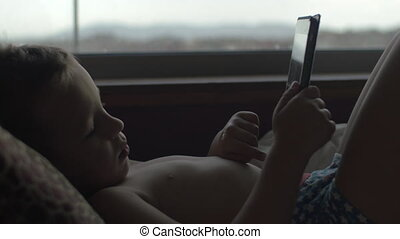 Child using digital tablet in bed - Boy in pants lying in...