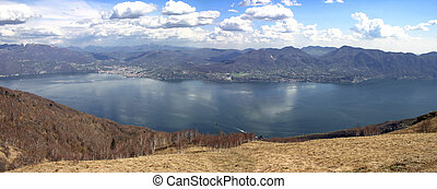 Panorama of Maggiore lake in Italy with blue aky and clouds...