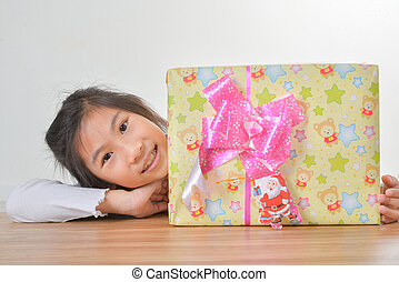 Cute Asian girl with gift and looking up something on a gray...
