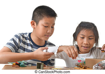 Asian boy and girl playing lego on white background.