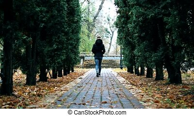 Teenager girl in jeans and black jacket walks in park