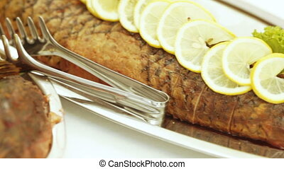 Fried pike with lemon - On table dish with fried pike and...