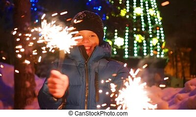 The child holds the sparklers outdoors in the winter. Slowmotion . In the background, lights and garlands of Christmas fir