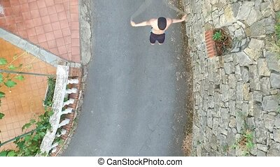 Shirtless athletic young man jumping rope in road -...