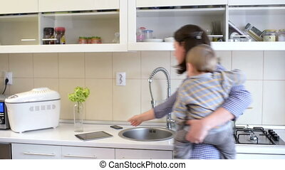 Busy Mother in Kitchen - Beautiful young mother holding a...