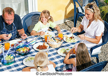 Family eating in the garden - Family having dinner in their...