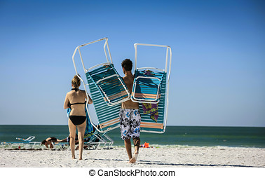 People carrying sun loungers on the beach at Siesta Key in Sarasota FL