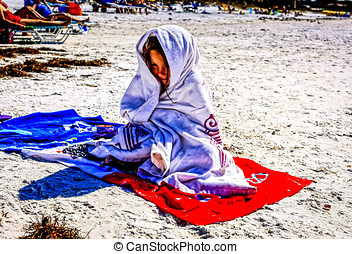 Young girl wrapped in a towel on Siesta Key Beach FL