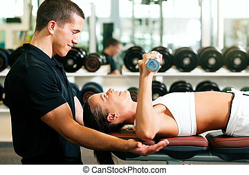 Personal Trainer in gym - Woman with her personal fitness...