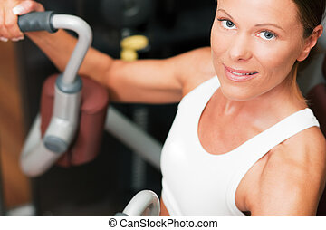 Woman in gym on machine - Woman doing fitness training on a...