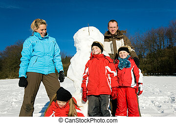 Family in winter standing in front of their snowman