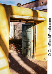 Yellow adobe srchway with an old green door in Santa Fe NM -...